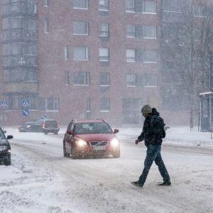 Jalankulkija lumisateessa.
