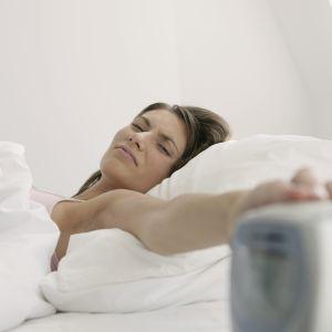 Nainen sammuttaa herätyskelloa.