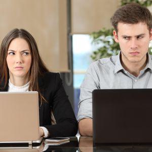 Kaksi henkilöä toimistossa kyräilevät toisiaan.
