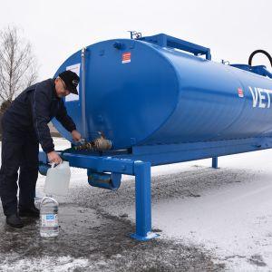 Mies täyttää vesikanisteria Nousiaisten kuntaan tuodusta vesisäiliöstä.