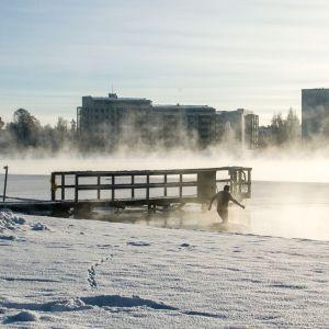 Mies menee Oulujokeen uimaan talvella
