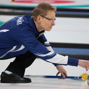 Tomi Rantamäki tähtää curlingjäällä.