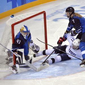 Noora Räty torjuu, kun USA:n Jocelyne Lamoureux-Davidson ja Suomen Mira Jalosuo vääntävät kiekosta.