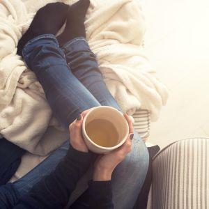 Nainen sohvalla kahvikuppi kädessä.