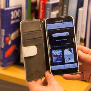 Kännykän käyttäjä selailee elokuvia kirjaston uudessa Viddla-palvelussa.