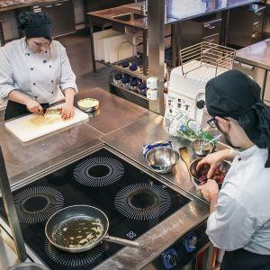 Kokkioppilaat kokkaavat pilkkovat sipulia ja maustavat lihaa lieden äärellä
