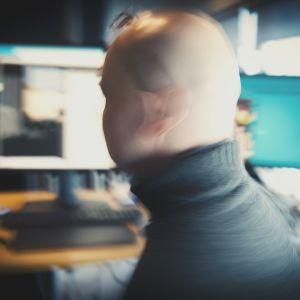 Mies tietokoneen monitorien edessä liikkeestä epäselvänä hahmona.