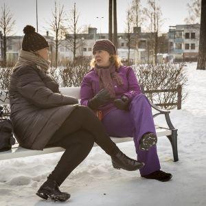 Äitimentori Tiina Tervonen ja perheenäiti Heini Mielonen juttelevat puiston penkillä.