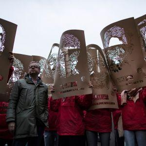 Pariisissa mielenosoitus Turkissa vangittujen toimittajien puolesta. Mielenosoittajien käsissä paperista leikattuja kasvokuvia.