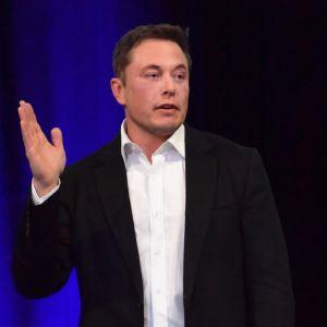 Teslan toimitusjohtaja Elon Musk puhuu, hänen oikea kätensä on viittausasennossa.