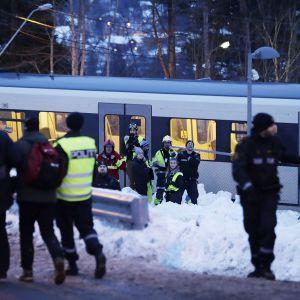 ihmisiä junan edustalla ja poliiseja