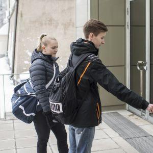 Kaksi oppilasta menossa koulurakennukseen.