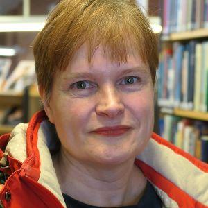 Nainen on kirjastossa ja katsoo kameraan.
