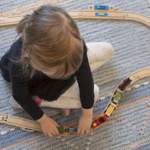 Päiväkotityttö leikkii junaradalla.