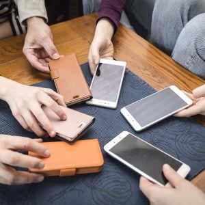 Kuuden hengen perheen puhelimet pöydällä.