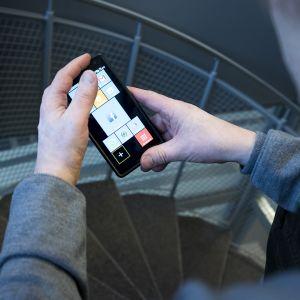 Mies katselee puhelinta jossa eri aplikaatioita.