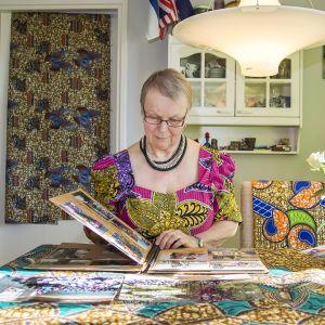 Nainen istuu pöydän ääressä ja selailee valokuva-albumia.