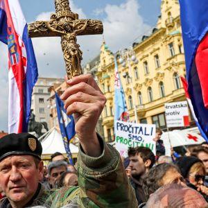 ihmisiä lippujen ja ristien kanssa