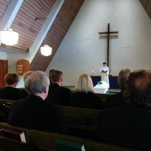 Hautajaisväki istuu Honkanummen kappelin pitkissä penkeissä. Valkoiseen kaapuun pukeutunut naispappi seisoo valkoisen arkun vieressä raamattu kädessä. Arkun päällä on yksinkertainen kukkakimppu.