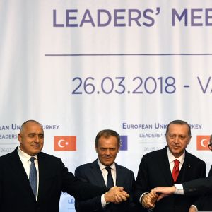 Kuvassa neljä huippukokukseen osallistunutta johtajaa vierekkäin. Pitelevät toisiaan kädestä, ehkä hieman kättelevät.