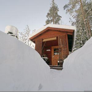 Korkeat lumikinokset pihasaunan ympärillä Joensuussa.