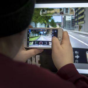 Nuori mies kuvaa kännykällä tietokonenäyttöä