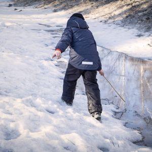 Lapsi leikkii lumessa
