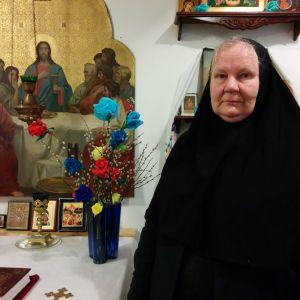 Mustaan nunnanviittaan pukeutunut nunna Elisabet seisoo Mikonkadulla sijaitsevan pienen ortodoksikappelin alttarin edessä. Taustalla ikoneita ja itäiseentyyliin tehtyjä virpomisvitsoja, joissa on silkkipaperista tehtyjä eri värisiä kukkia. Pöydällä on myös raamattu ja koristeellinen kynttilänjalka.