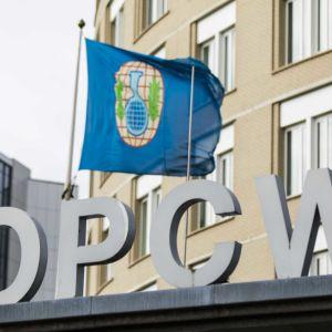 Kuvassa OPCW:n logo ja lippu, joka heiluu päämajan fasadissa.