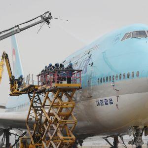 Työntekijät kuurasivat Korean Airin konetta puhtaaksi Incheonin lentokentällä Etelä-Koreassa 6. huhtikuuta 2018.