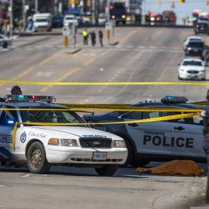 Poliisiautoja eristetyn alueen reunalla, poliisi on eristänyt alueen keltaisin nauhoin.