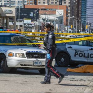 Naispoliisi kävelee eristysalueen reunalla, takana näkyy poliisiautoja ja suljettu katu.