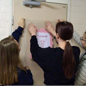Oppilaat kiinnittämässä merkkiä koulun vessan oveen.