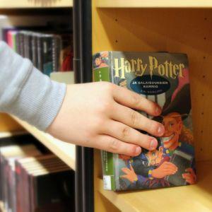 Käsi nostaa kirjaston hyllystä Harry Potter -kirjan.