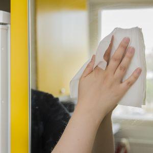 Nainen pyykii peilin pinnasta pölyt pois.