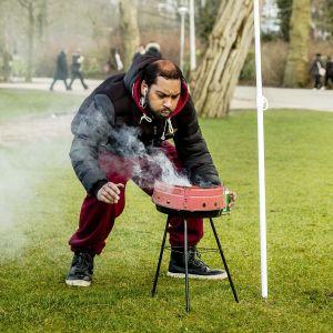 Mies puhaltaa grilliin.