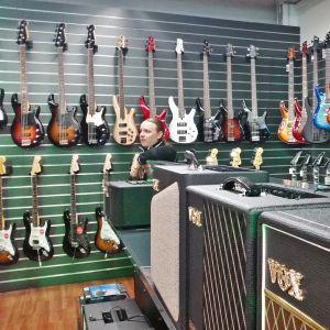 Musiikkikauppias Kalle Ruumensaari kaupan kitarakokoelman keskellä.