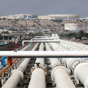 Öljyputkia ja öljysäiliöitä rannalla.