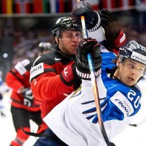 Sebastian Aho kamppailee Kanadan Ryan Murrayta vastaan.