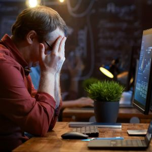mies ahdistuneena tietokoneen edessä