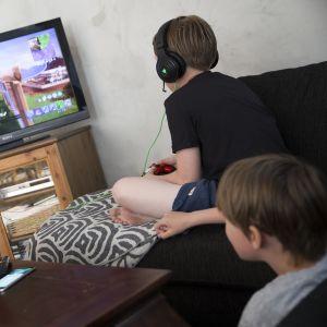 Pojat pelaavat pelikonsolilla.
