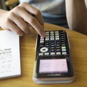 Nuori laskee matematiikan tehtäviä funktiolaskimella.