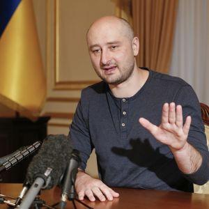 Kuvassa Arkadi Babtšenko istuu pöydän takana. Hänen vasen kätensä on pystyssä. Pöydällä hänen edessään on mikrofoneja.