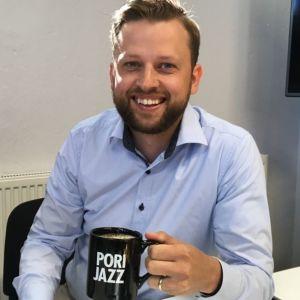 Mies hymyilee ja pitää kädessään Pori Jazz -kahvikuppia.