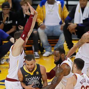 Golden Staten Stephen Curry  pitää palloa Clevelandin LeBron Jamesin ja Kyle Korven välissä.