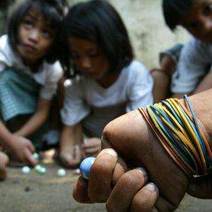 Filippiiniläislapset leikkivät marmorikuulilla Manilan lähiössä maaliskuussa 2004.