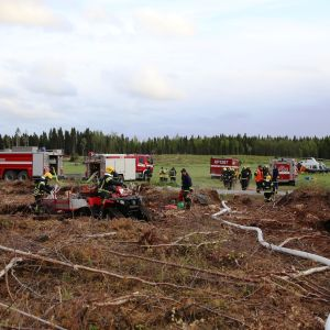 Pelastuslaitoksen henkilöstöä ja ajoneuvoja maastossa palopaikalla.