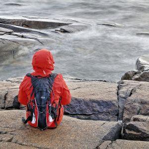 yksinäinen nainen rantakalliolla
