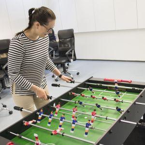 Kuvassa työkykykoordinaattori Kristiina Hentilä pelaa pöytäjalkapalloa.