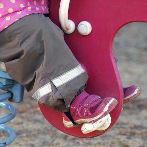 Lapsi keinuu leikkipuistossa.